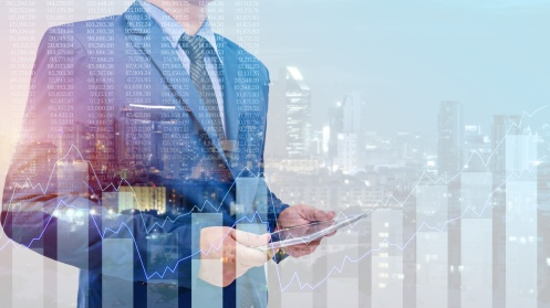 Double exposure of business man using tablet with cityscape back